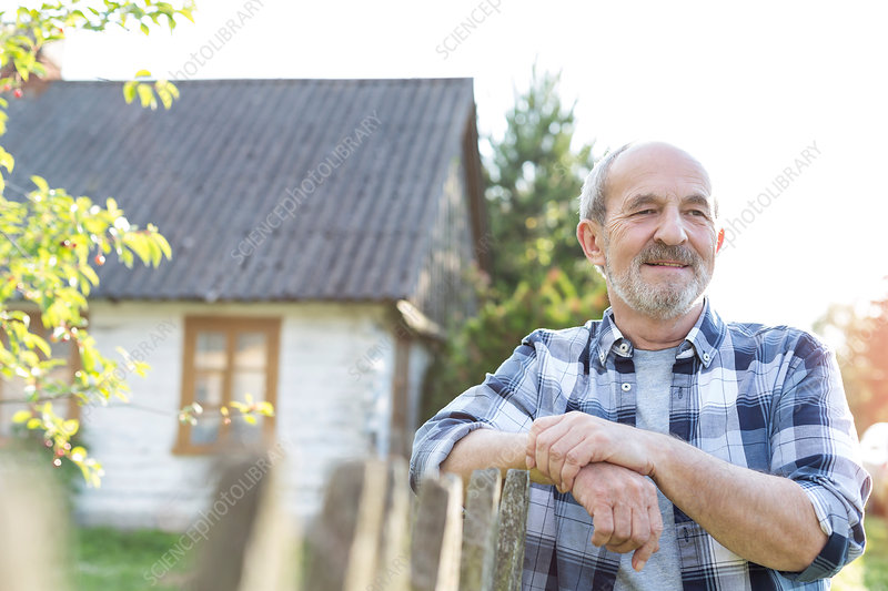 Confident farmer leaning on fence