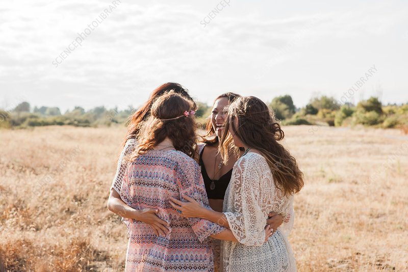 Boho women hugging in rural field