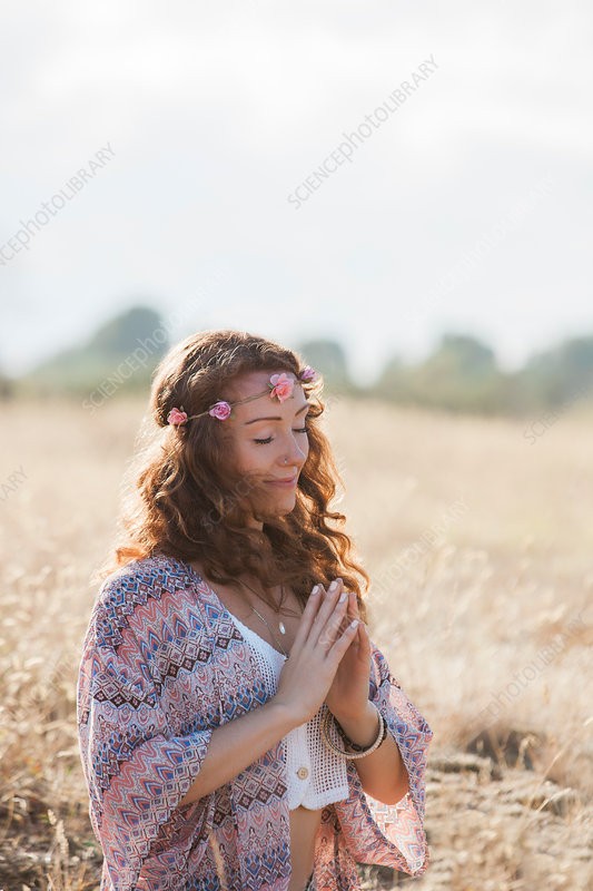 Serene boho woman meditating with hands