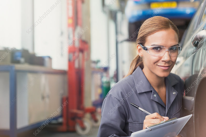 Confident female mechanic with clipboard