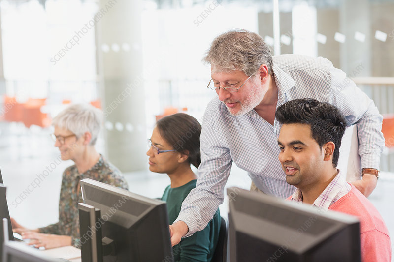 Professor helping student at computer