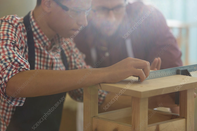 Carpenters measuring wood with ruler