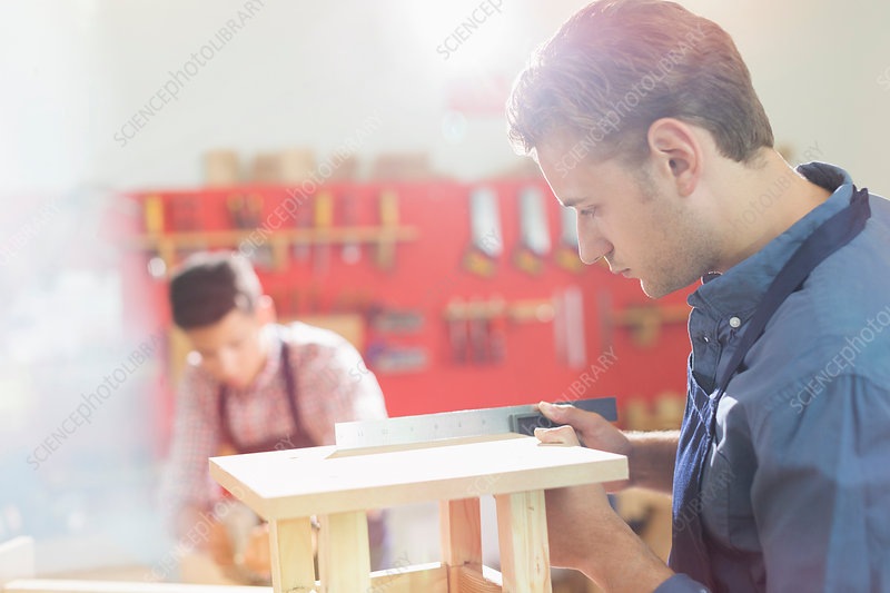 Carpenter measuring wood with ruler