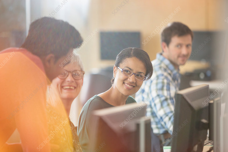 Smiling students talking at computers