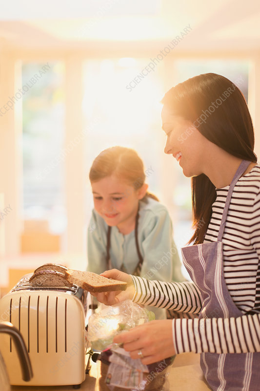Mother and daughter toasting bread