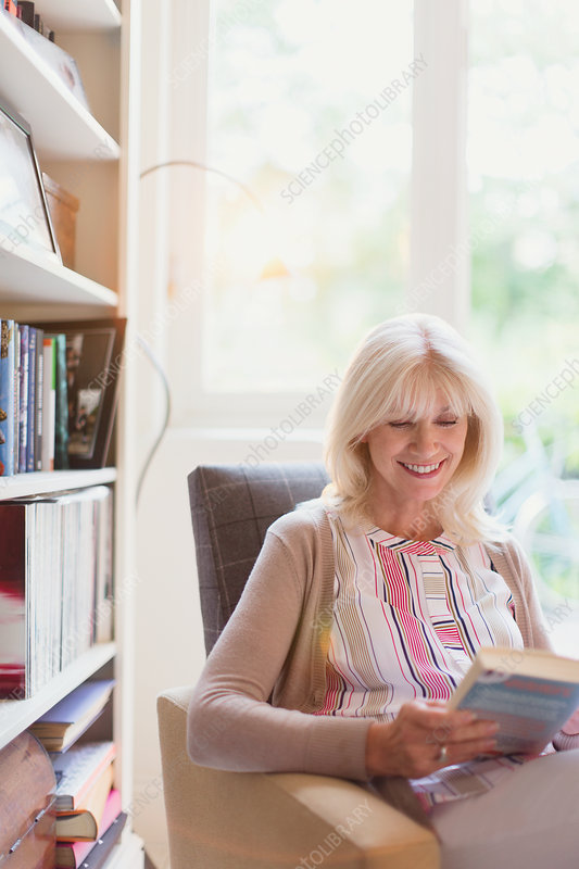 Smiling senior woman reading book in den