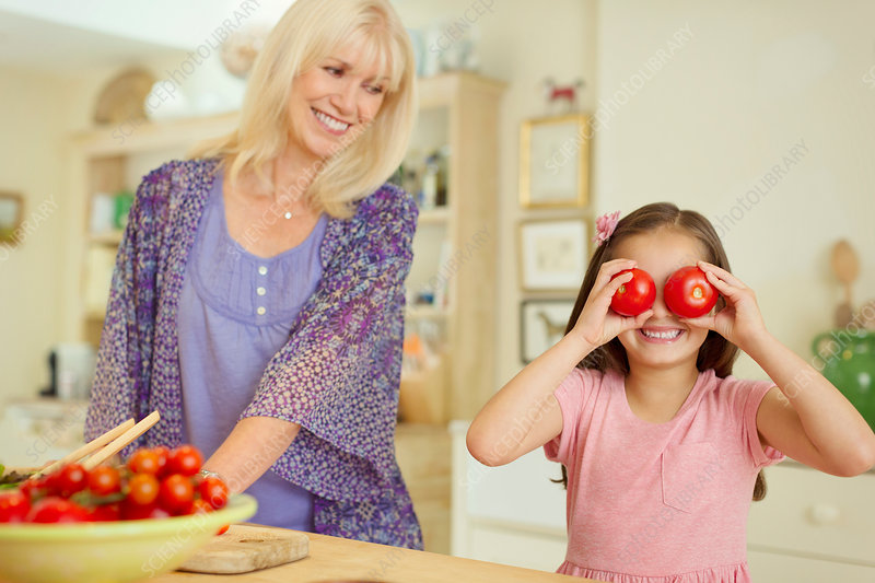Playful girl covering eyes with tomatoes