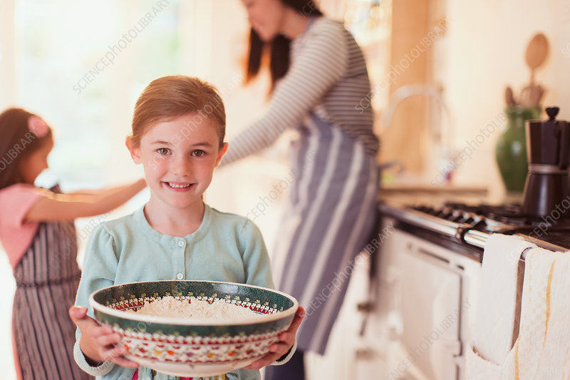 Smiling girl baking holding bowl of flour