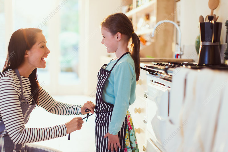 Mother tying apron on daughter in kitchen