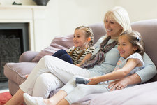 Grandmother and granddaughters on sofa