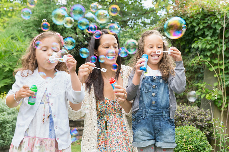 Mother and daughters blowing bubbles