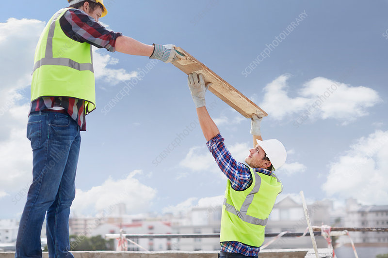 Construction workers lifting part
