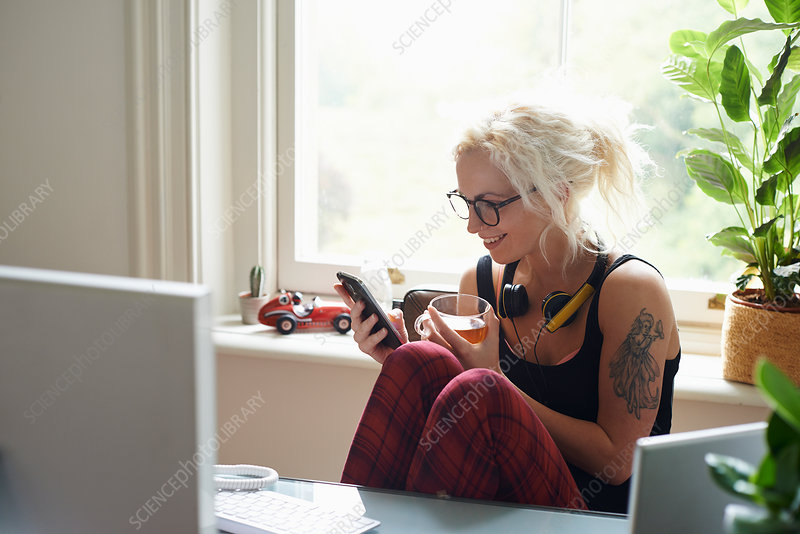 Young woman texting in home office