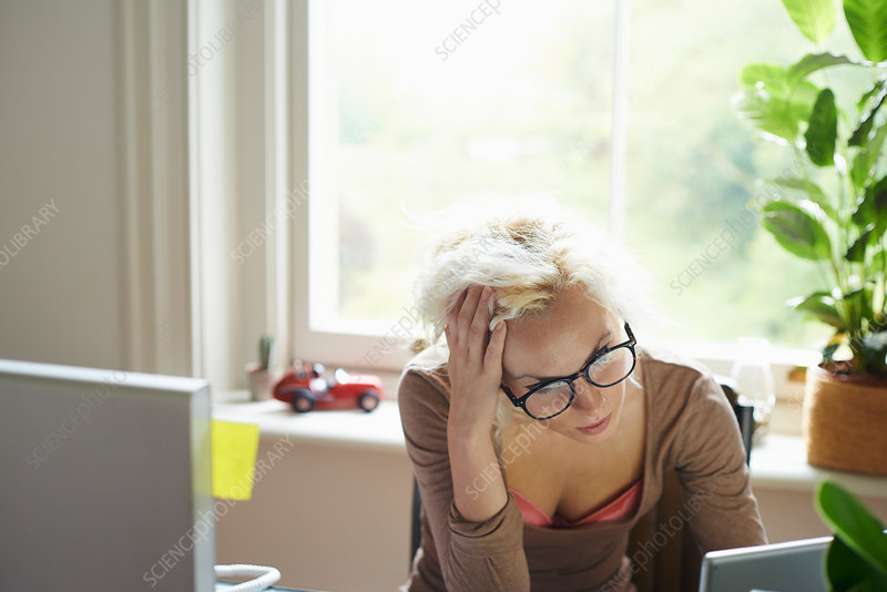 Stressed woman with hands in hair working