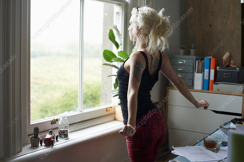 Young woman stretching at window