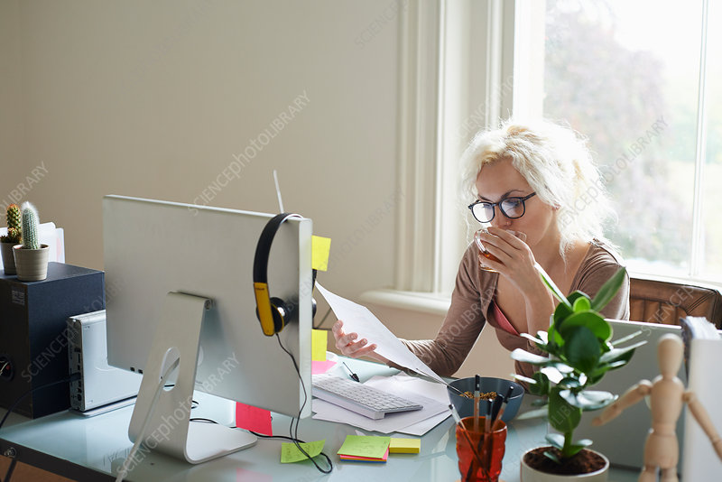 Young woman drinking tea in home office