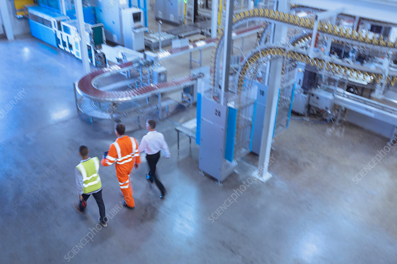 Workers and supervisor walking in factory