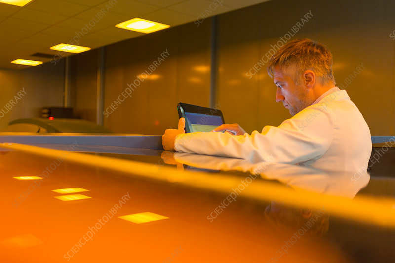 Worker at touch screen in factory