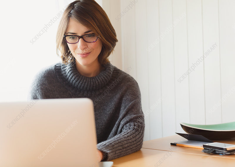 Woman in sweater using laptop at table