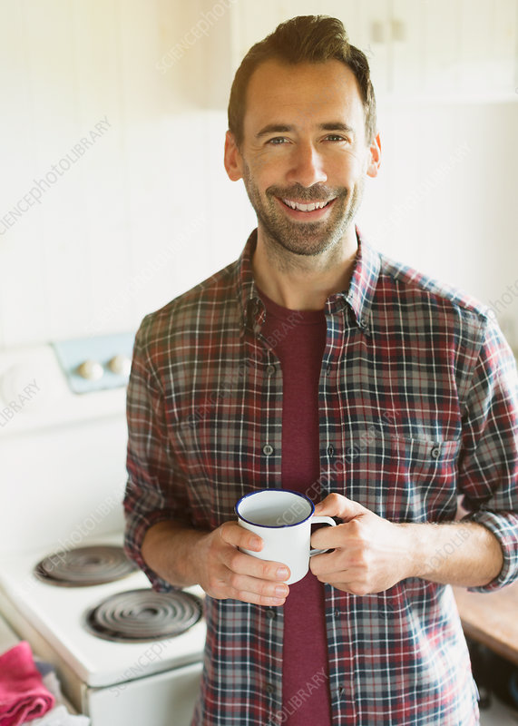 Brunette man drinking coffee in kitchen