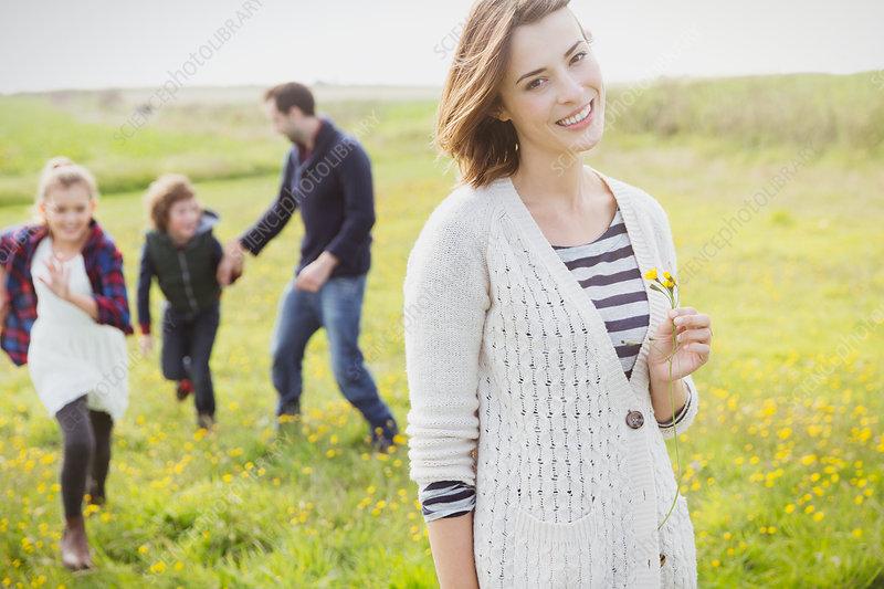 Woman holding wildflower with family