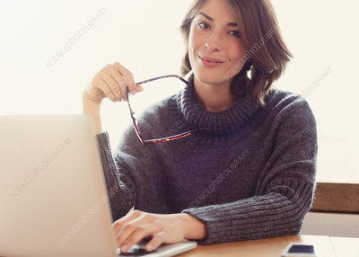 Woman holding eyeglasses with laptop