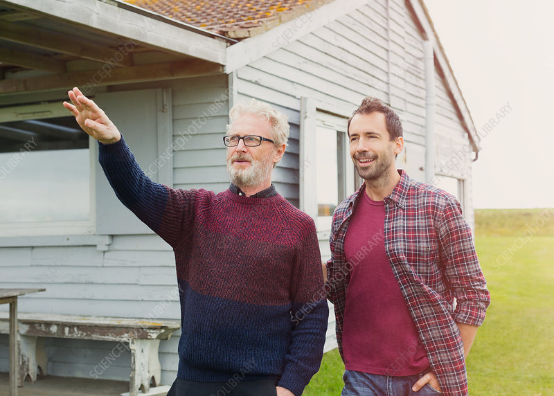Father gesturing to son outside house