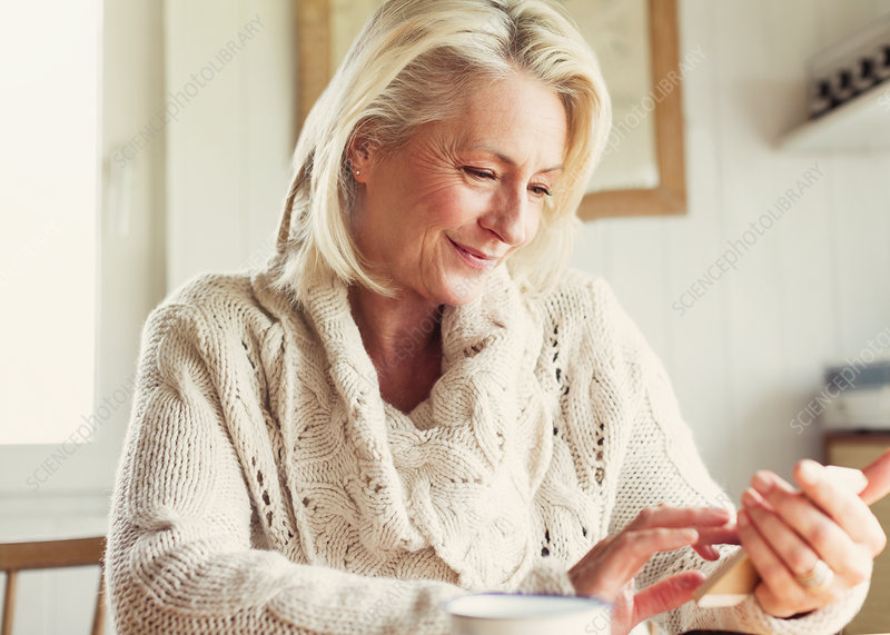 Senior woman in sweater texting