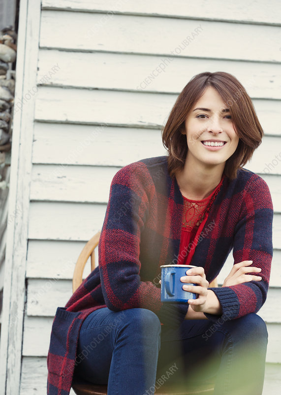Brunette woman drinking coffee outdoors