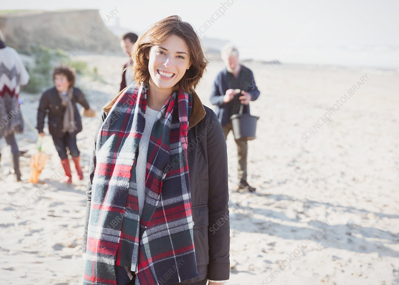 Woman in plaid scarf with family on beach