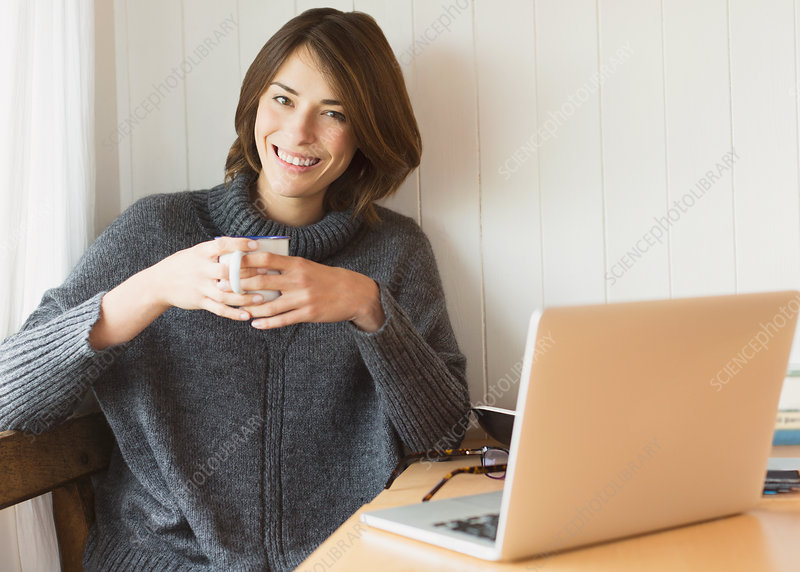 Woman drinking coffee at laptop
