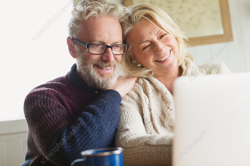 Senior couple using laptop in kitchen