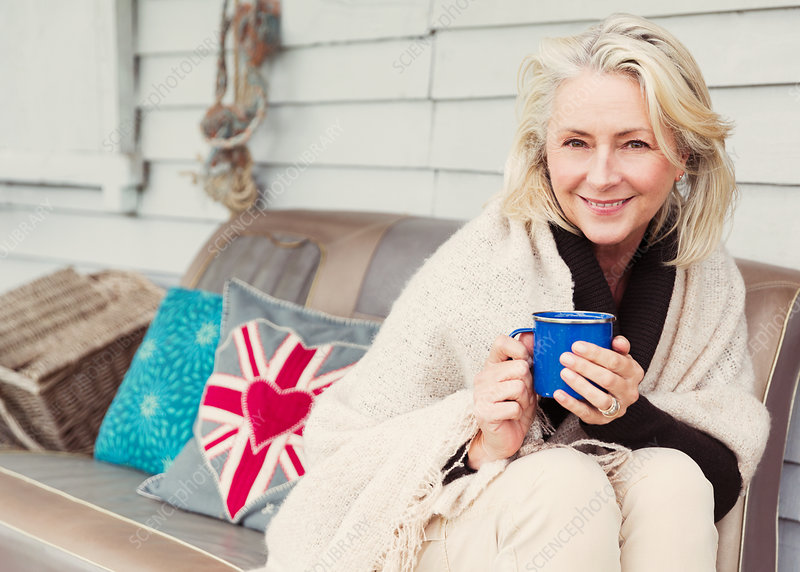 Senior woman drinking coffee sofa
