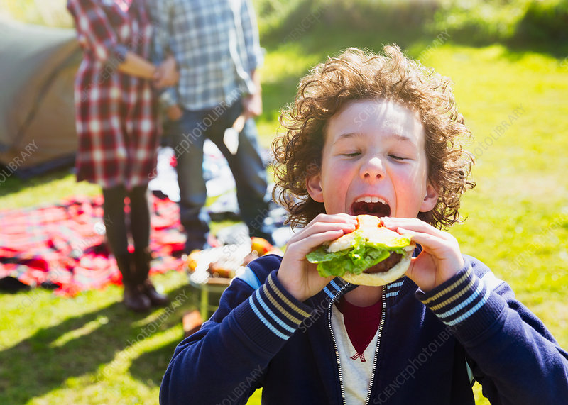 Boy taking large bite of hamburger
