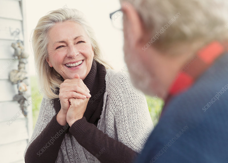 Smiling senior woman talking to man