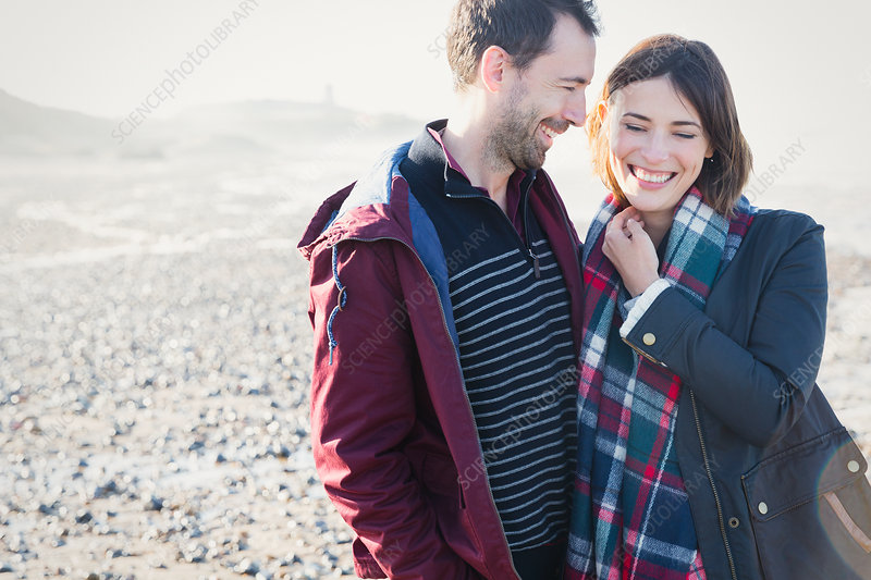 Couple standing on sunny rocky beach