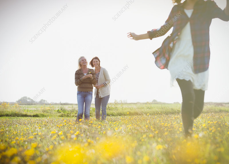 Women watching girl run in meadow