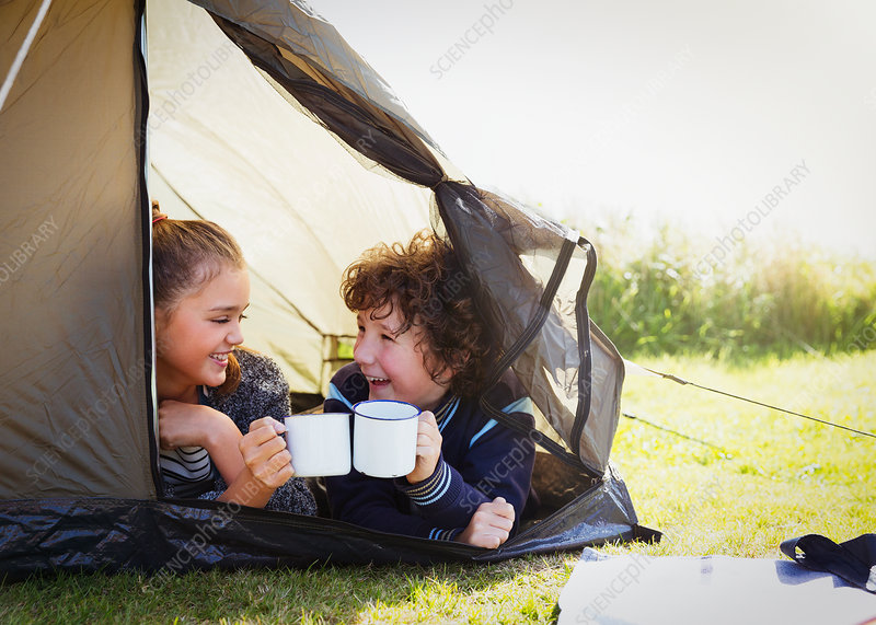 Brother and sister toasting mugs in tent
