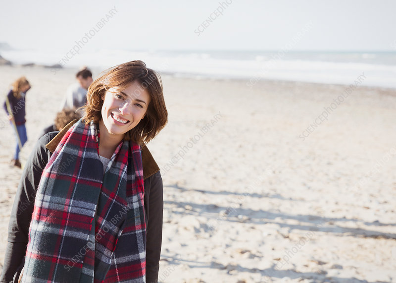 Woman in plaid scarf on sunny beach