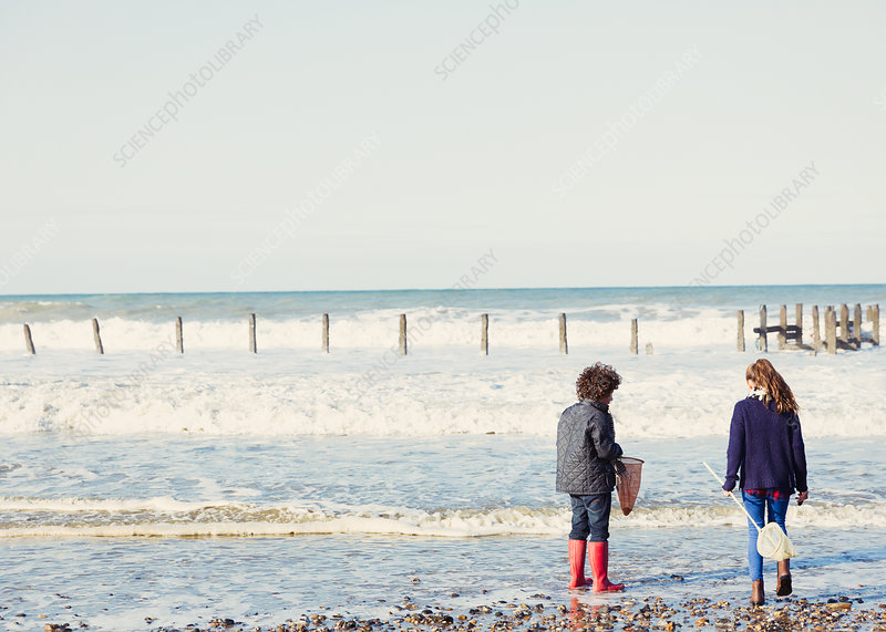 Brother and sister with nets in ocean