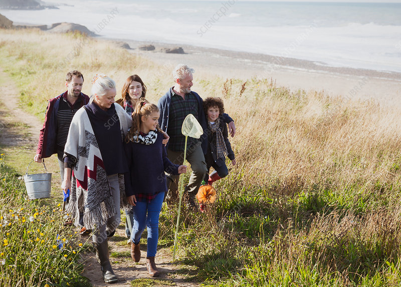 Family with nets and bucket on beach path