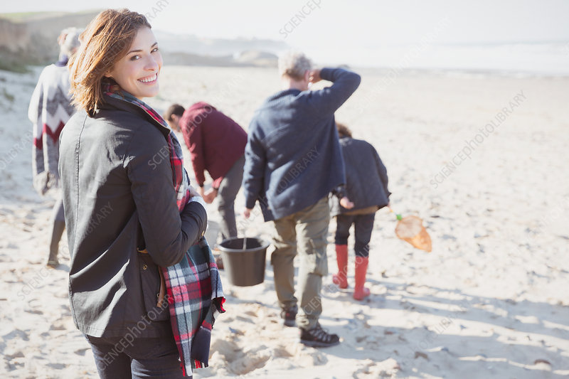 Woman walking on sunny beach with family
