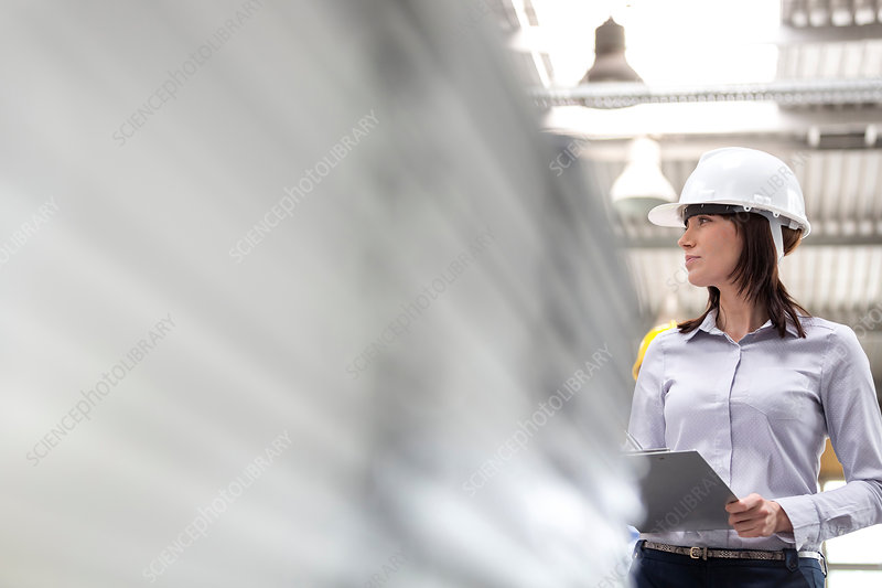 Businesswoman in hard-hat and clipboard