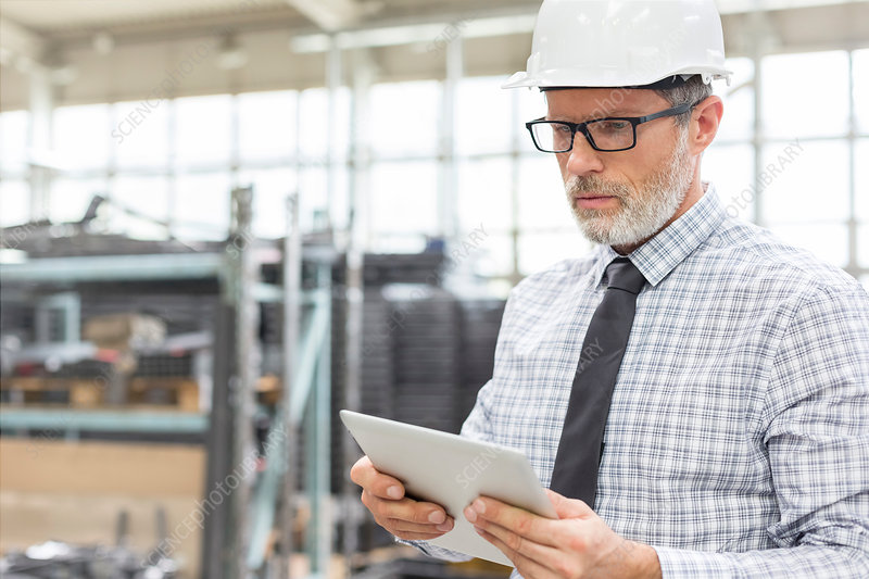Engineer using digital tablet in factory