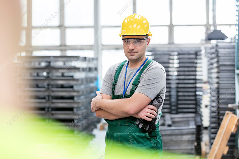 Worker with arms crossed in factory