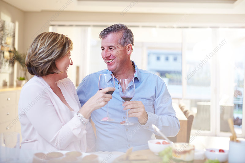 Couple toasting red wine glasses