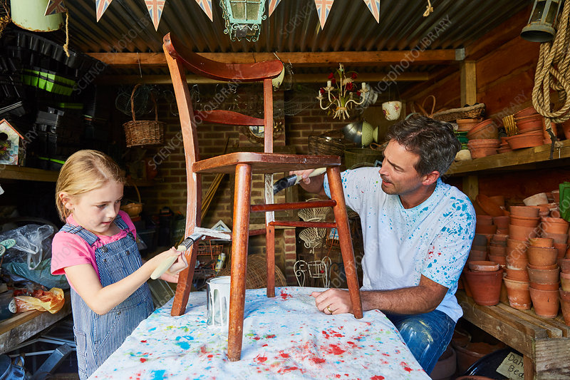 Father and daughter painting chair