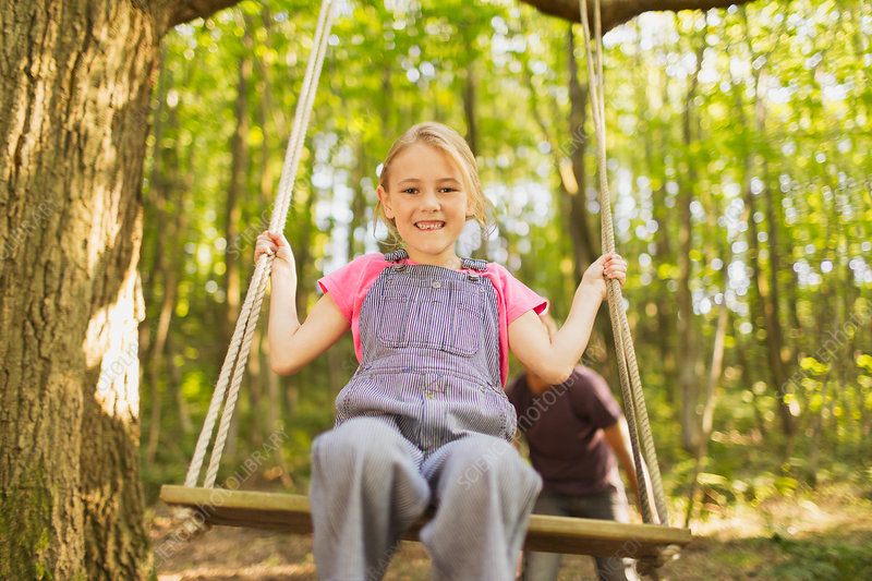 Girl swinging on rope swing in forest