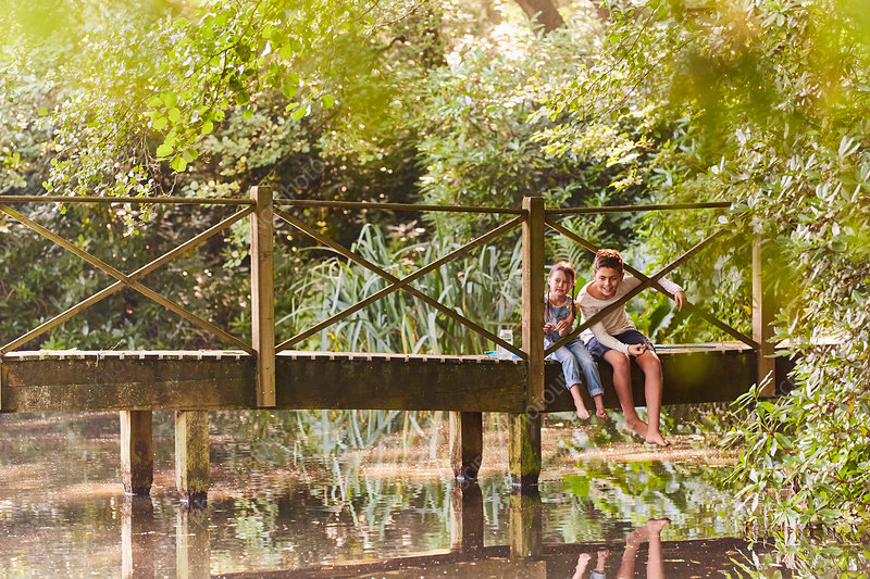 Brother and sister sitting on footbridge