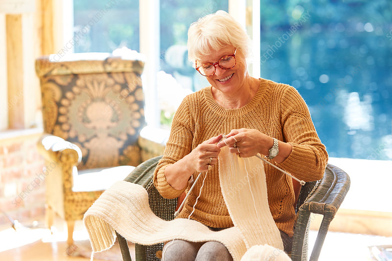 Senior woman knitting in living room